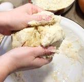 Mains malaxant la pâte de pain Photo stock
