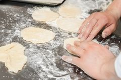 Mains malaxant la pâte sur la surface floured photographie stock libre de droits