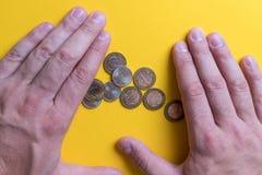 Mains masculines autour des pièces de monnaie Protection de votre argent Manque d'argent Plan des dépenses photos stock