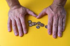 Mains masculines autour des pièces de monnaie Protection de votre argent Manque d'argent Plan des dépenses images stock