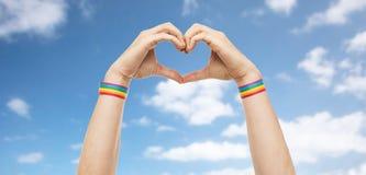 Mains masculines avec des bracelets de fierté gaie montrant le coeur Images libres de droits