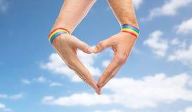 Mains masculines avec des bracelets de fierté gaie montrant le coeur Images stock