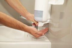 Mains masculines avec l'utilisation de distributeur de savon dans les toilettes photographie stock libre de droits