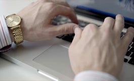 Mains masculines avec la montre d'or au-dessus d'un clavier d'ordinateur portable images libres de droits