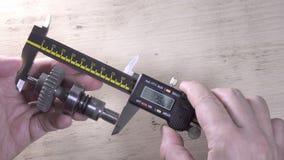 Mains masculines avec le calibre numérique, processus de la mesure d'un détail banque de vidéos