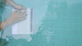 Mains masculines avec un fonctionnement d'ordinateur portable sous l'eau Le concept de l'obstruction dans le travail Fond abstrai banque de vidéos
