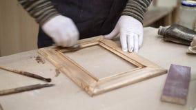 Mains masculines avec un petit pinceau huilant le cadre en bois se trouvant sur la table banque de vidéos