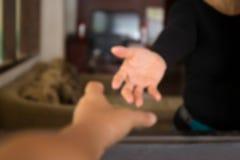 Mains masculines brouillées de concept atteignant pour aider la femme image libre de droits