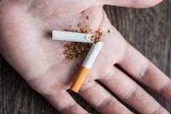 Mains masculines cassant une cigarette Photos libres de droits