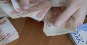 Mains masculines comptant l'argent Billets de banque russes d'argent de 5 000 roubles banque de vidéos