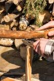 Mains masculines dédoublant le bois avec le couteau Images stock