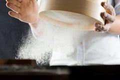 Mains masculines d'un cuisinier tamisant la farine au travers d'un tamis dans la cuisine image libre de droits