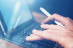 Mains masculines dactylographiant sur la station électronique de clavier-dock de comprimé Équipez le travail au bureau tout en se photographie stock
