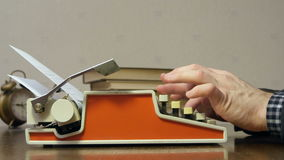 Mains masculines dactylographiant sur la vieille machine à écrire rouge au bureau avec des livres clips vidéos