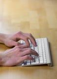 Mains masculines dactylographiant sur le clavier sans fil sur le bureau en bois photos libres de droits