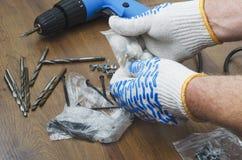 Mains masculines dans les gants choisissant des vis pour le tournevis Concept de la rénovation dans la maison images stock