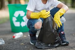 Mains masculines dans les gants en caoutchouc jaunes mettant des déchets de ménage dans le petit et noir sac de poubelle dehors photos stock