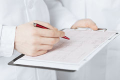 Mains masculines de docteur tenant le cardiogramme Image libre de droits