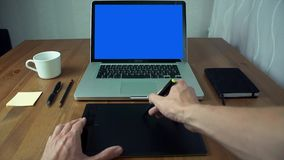 Mains masculines de vue de POV utilisant l'étiquette et l'ordinateur portable graphiques avec l'écran vert au bureau blanc banque de vidéos