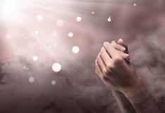 Mains masculines en position de prière avec le rayon image stock