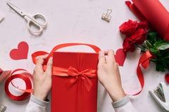Mains masculines enveloppant le présent fait main de Valentine en papier avec le rouge Photographie stock