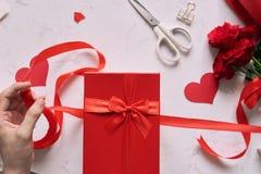 Mains masculines enveloppant le présent fait main de Valentine en papier avec le rouge Images stock