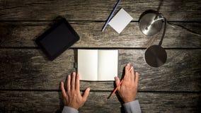 Mains masculines environ pour faire des notes dans le carnet vide Image stock