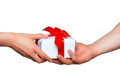 Mains masculines et femelles avec le boîte-cadeau blanc avec l'arc Image stock