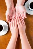 Mains masculines et femelles sur la table avec des tasses Photo stock