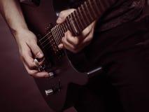 Mains masculines jouant la guitare électrique image stock