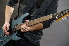 Mains masculines jouant la guitare électrique image libre de droits