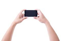 Mains masculines jugeant le téléphone intelligent mobile avec l'écran vide d'isolement Photo libre de droits