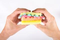 Mains masculines jugeant un hamburger fait à partir de différentes couleurs d'éponges Concept de nourriture malsaine et de produi Images libres de droits
