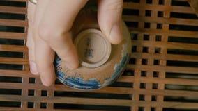 Mains masculines mettant le bol de thé à l'envers sur la table de thé en bois après le boire clips vidéos