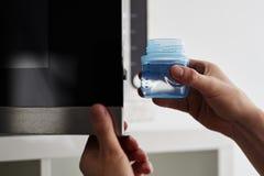 Mains masculines mettant un biberon avec de l'eau dans une micro-onde photo stock