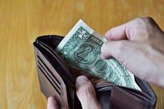 Mains masculines ouvrant un portefeuille en cuir presque vide avec seulement un dollar américain (un dollar US d'USD,) comme symb Image stock
