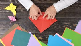 Mains masculines pliant la feuille de papier rouge photo libre de droits