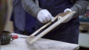 Mains masculines polissant le cadre en bois dans le studio de travail du bois banque de vidéos