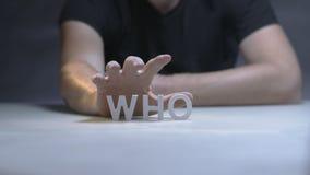 Mains masculines prenant le mot de mains qui a composé des lettres blanches sur le fond gris banque de vidéos