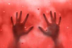 Mains masculines sur la fenêtre avec des formes de coeur Photo stock
