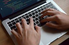 Mains masculines sur un clavier noir Codage européen sur un ordinateur S photo libre de droits