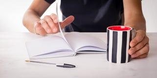 Mains masculines sur une table avec la tasse et les livres Photo libre de droits