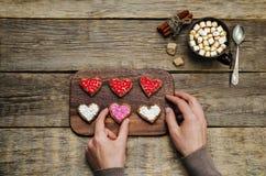 Mains masculines tenant des biscuits sous les formes de coeur Photographie stock