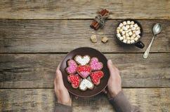 Mains masculines tenant des biscuits sous les formes de coeur Photos stock