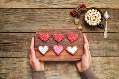 Mains masculines tenant des biscuits sous les formes de coeur Image stock