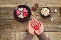 Mains masculines tenant des biscuits sous les formes de coeur Images libres de droits