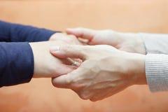 Mains masculines tenant des mains d'amie Soin et amour Images stock