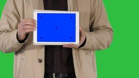 Mains masculines tenant le comprimé avec la maquette d'écran bleu sur un écran vert, clé de chroma banque de vidéos