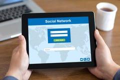 Mains masculines tenant le comprimé avec le réseau social sur l'écran Images libres de droits