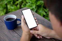 Mains masculines tenant le téléphone avec un écran d'isolement en café Image libre de droits